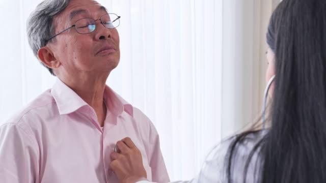 アジアの女性医師が診察室で患者の心臓シニア男性をチェックし、アジアのシニア男性が医療専門家による健康診断を受ける。 - 年次イベント点の映像素材/bロール