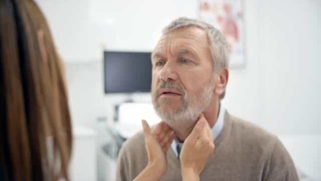 asian female doctor checking the senior male patient's lymph nodes - lymph node stock videos & royalty-free footage