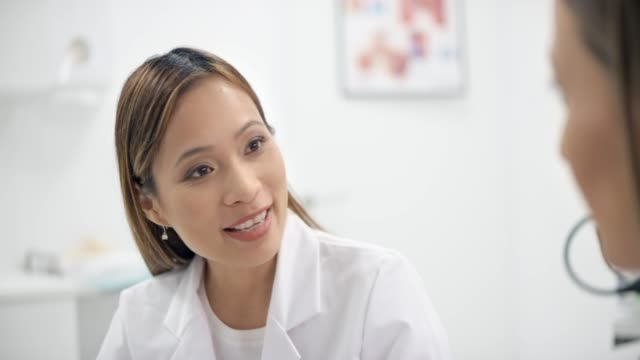 asian female doctor talking to her patient in her office - part of a series stock videos & royalty-free footage