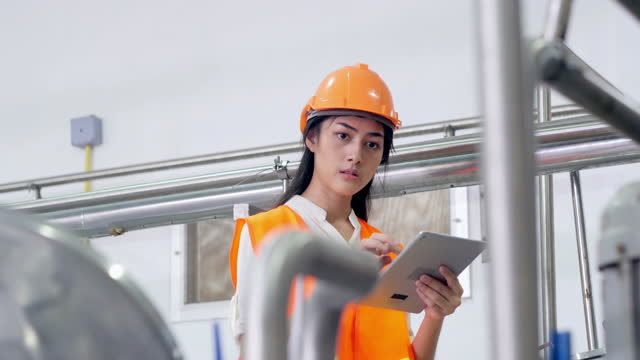 asian female engineer in hard hat wearing safety uses touchscreen tablet computer to the work process of the heavy industrial.women in stem - examining stock videos & royalty-free footage