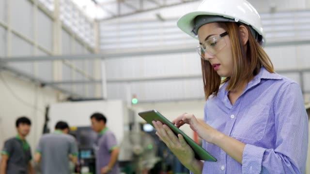 vídeos de stock, filmes e b-roll de engenheira asiática inspecionando máquinas em um local de trabalho industrial - foco determinação