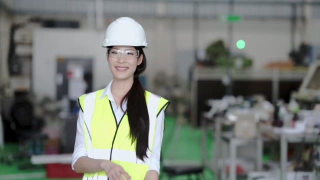 asian female engineer standing at industrial factory - manufacturing machinery stock videos & royalty-free footage