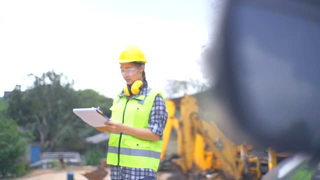 asian female engineer standing next to a ladle of a excavator and examines a scheme - ladle stock videos & royalty-free footage