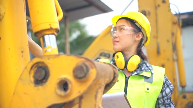 asian female engineer standing next to a ladle of a excavator and examines a scheme - pala meccanica video stock e b–roll