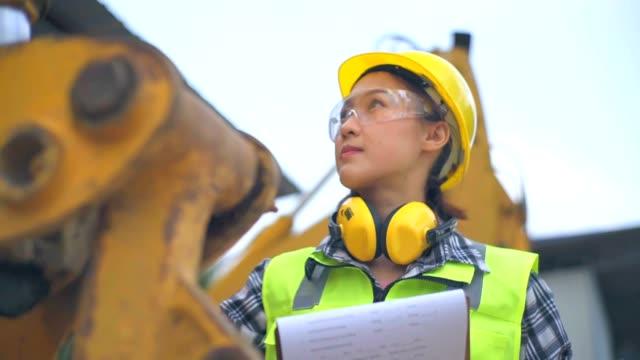 ingegnere femminile asiatico in piedi accanto a un siviere di un escavatore ed esamina uno schema - pala meccanica video stock e b–roll