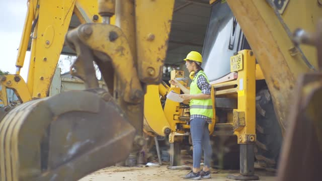 asian female engineer standing next to a ladle of a excavator and examines a scheme - mechanical digger stock videos & royalty-free footage