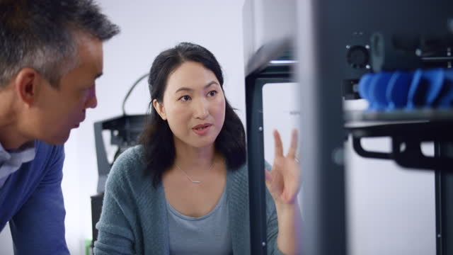 asian female engineer talking about the progress of a model construction with her male asian colleague as they stand by the 3d printer - industrial equipment stock videos & royalty-free footage