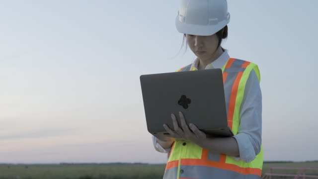 asian female engineer working on laptop at oil field - health and safety stock videos & royalty-free footage