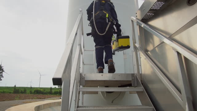 asian female engineers in uniform inspection engineers preparing and progress check of a wind turbine with safety in wind farm in thailand. - engineer stock videos & royalty-free footage