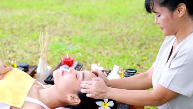 stockvideo's en b-roll-footage met asian female enjoy thai spa head massage in the garden - massagetafel