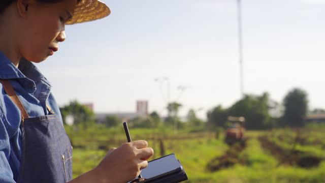 vidéos et rushes de agricultrice asiatique utilisant l'ordinateur portatif de tablette pour inspecter le moteur agricole dans les terres agricoles - ingénieur