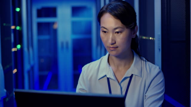 ds asian female it engineer checking the server operations using her laptop in the server room - conformity stock videos & royalty-free footage