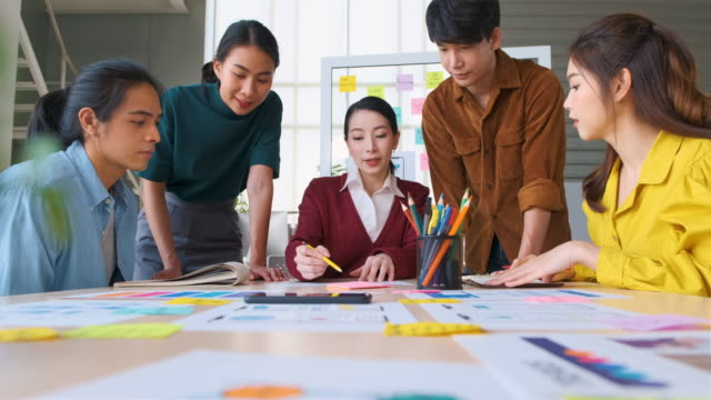 asian female leader advice ux/ui designer about mobile app interface wireframe design on table at modern office.creative digital development agency - sales pitch stock videos & royalty-free footage