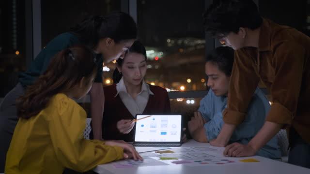 アジアの女性リーダーは、夜に近代的なオフィスのテーブルの上にモバイルアプリインターフェイスワイヤーフレームデザインについてux / uiデザイナーにアドバイス.後期クリエイティブデ� - プロトタイプ点の映像素材/bロール