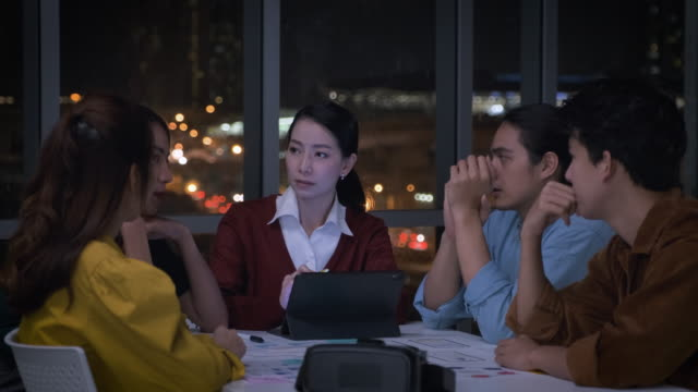 asian female leader and ux/ui designer serious meeting about deadline of mobile app interface wireframe design in modern office at night.working late creative digital development agency - scolding stock videos & royalty-free footage