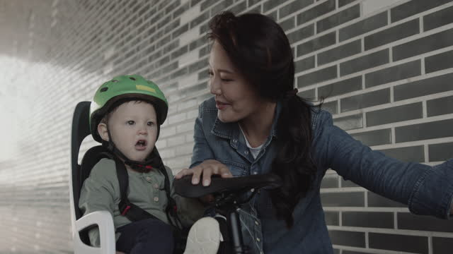 asian female mother with toddler in safety seat on bicycle - passenger seat stock videos & royalty-free footage