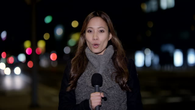 asian female news reporter reporting live from the city center at night - journalist video stock e b–roll