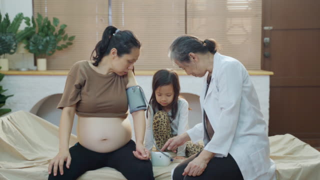 asian female nurse on the house call checking pregnant woman at home - house call stock videos & royalty-free footage