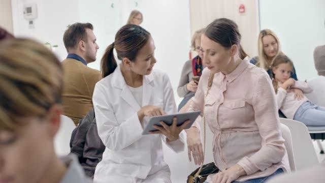 アジアの女性産婦人科医が最終的な結果に目を通すに待合室で彼女の妊娠中の患者の横に座って
