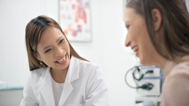 asian female ob-gyn smiling while talking to her pregnant patient and showing her the ultrasound photo on the computer - mid adult stock videos & royalty-free footage