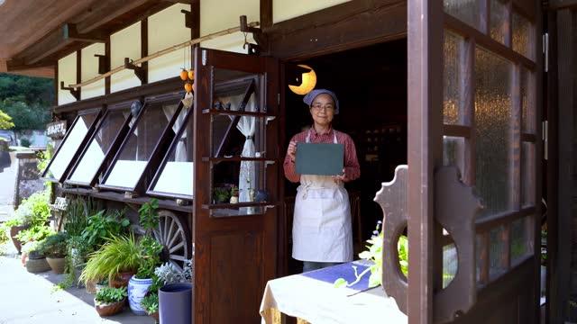 la proprietaria asiatica tiene in mano la lavagna vuota. - lingua giapponese video stock e b–roll