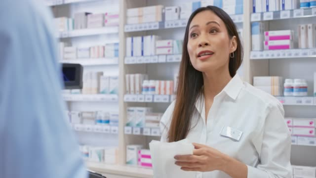 asian female pharmacists packing the medicine into a white bag and handing it to the customer - medical occupation stock videos & royalty-free footage
