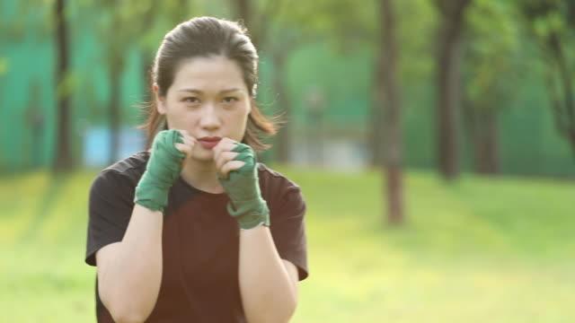 asian female practicing mixed martial art outdoor - カンフー点の映像素材/bロール