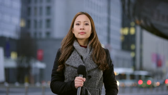 Asian female reporter live from the city center