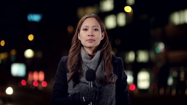 Asian female reporter reporting live from the city center at night
