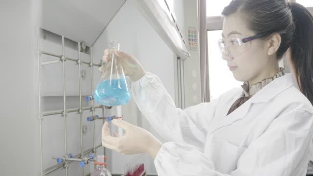 asian female scientist in chemical lab - pallone di vetro video stock e b–roll