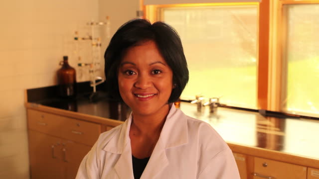 hd: asian female scientist, lab technician smiles to camera - smirking stock videos and b-roll footage