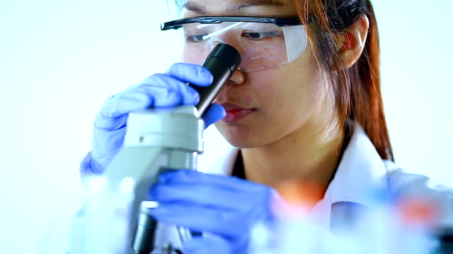 asian female scientist looks through a microscope in a laboratory