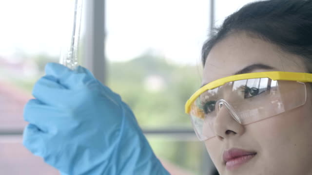 vídeos de stock e filmes b-roll de asian female scientist mixing chemical liquid in lab - material