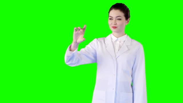 vídeos de stock, filmes e b-roll de asiática feminina cientista trabalhando com tela sensível ao toque. tela verde - gesticulando