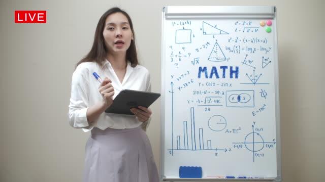 vídeos de stock e filmes b-roll de asian female teacher live math teaching remotely at home she talking on camera - workshop
