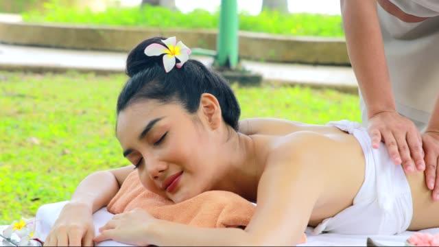 stockvideo's en b-roll-footage met asian female tourist enjoy thai spa massage with herb in the garden - massagetafel