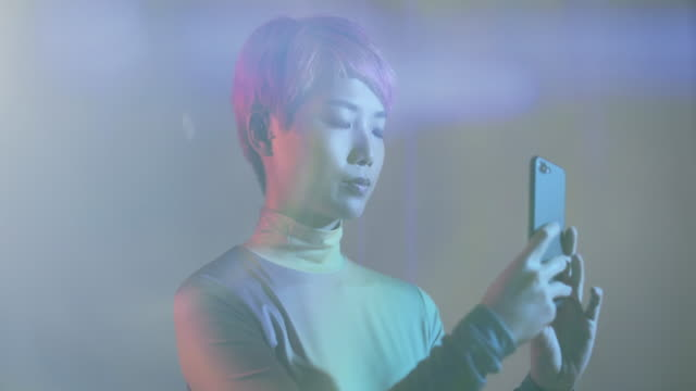 asian female using smart phone in futuristic environment - chinesischer abstammung stock-videos und b-roll-filmmaterial