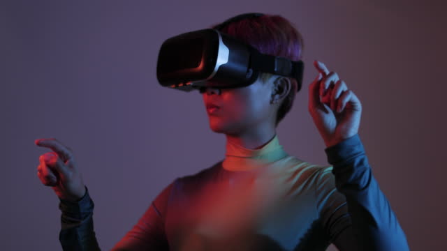vidéos et rushes de asian female using virtual reality technology in futuristic environment - perception sensorielle