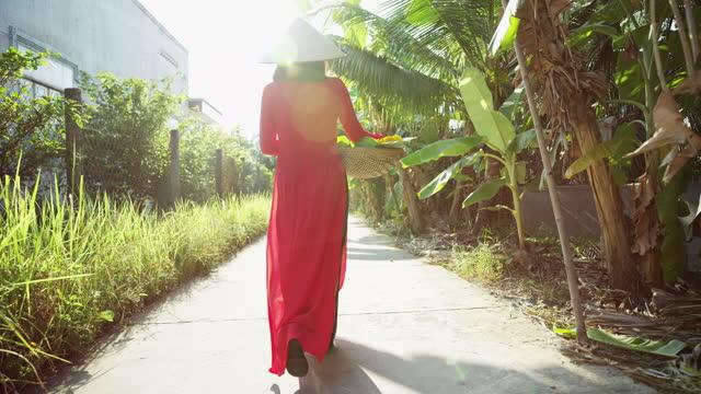 asian female walking with basket through plantation vietnam - 赤のドレス点の映像素材/bロール