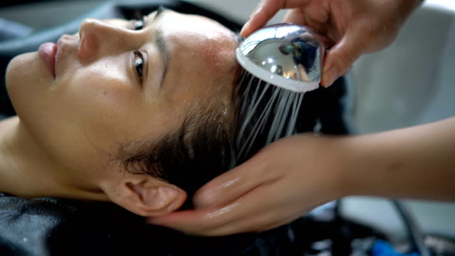 asian female washing hair in salon. - hair conditioner stock videos and b-roll footage