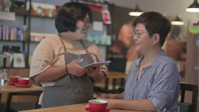 asian female with down syndrome waitress taking order from customer at cafe using digital tablet - persons with disabilities stock videos & royalty-free footage