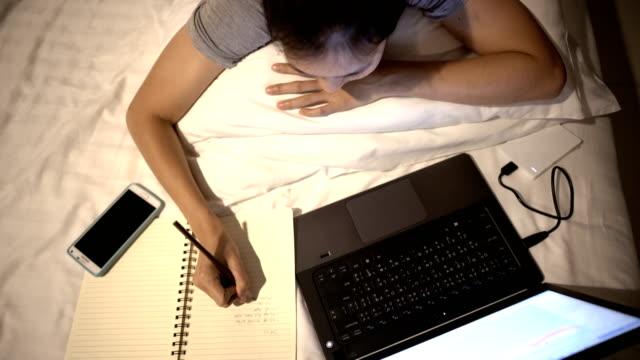vídeos y material grabado en eventos de stock de 4k mujer mujer asiática online trabajar-estudiar en cama por la noche. - estudio habitación