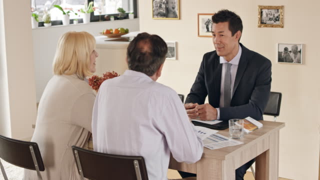 Asian financial advisor visiting an older couple at their home for consultation