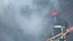 Asian fireman holding Axe confident walking through the smoke with fire burning hard in background. Firefighter career, Training fire drill Concept. Slow motion.