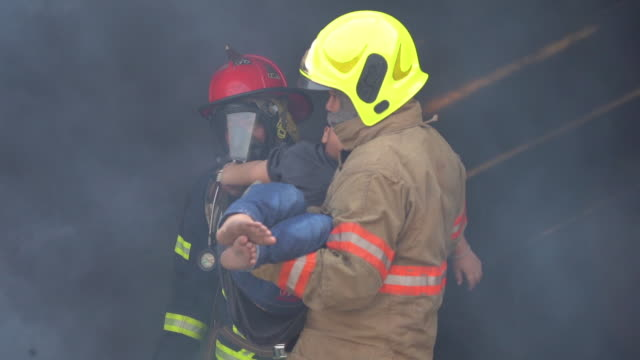 asian fireman wear fire protection suit with a saved boy in his arms and firefighter fighting with fire on a car during fire drill and helping fire victims concept. - fire protection suit stock videos & royalty-free footage