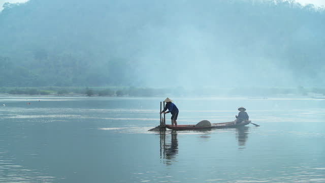 4k: asian fisherman on wooden boat casting a net for catching freshwater fish in nature river in the early morning before sunrise - netting stock videos and b-roll footage