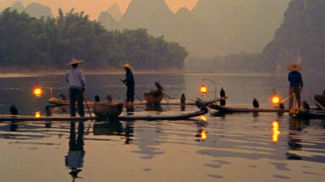 ORANGE PAN Asian fishermen on 'sampan' rafts with cormorant fishing birds + lanterns at dusk / China