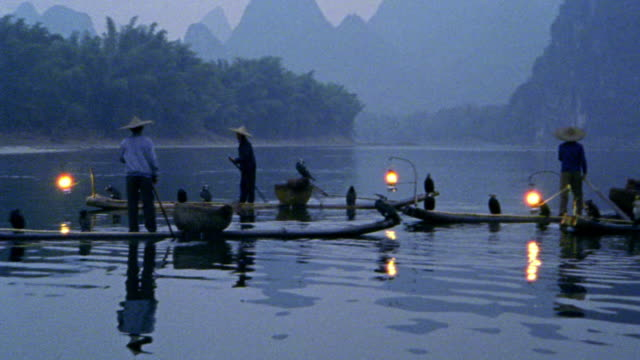 "pan asian fishermen on ""sampan"" rafts with cormorant fishing birds + lanterns at dusk / china - sampan stock videos & royalty-free footage"