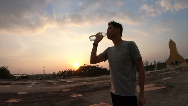 asian fitness man runner drinking water in bottle outdoors running jogging - bottle stock videos & royalty-free footage