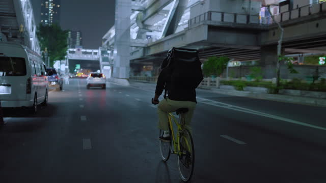 asian food courier cycling in the night - riding stock videos & royalty-free footage